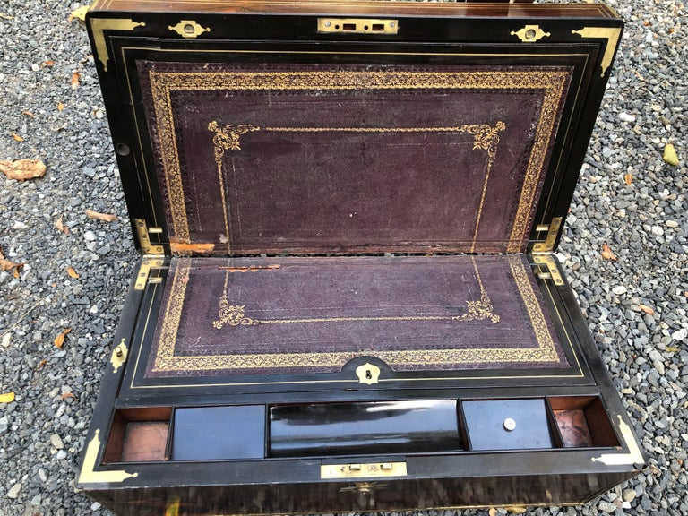 English mahogany lap desk, brass bound with inlaid brass stringing and brass presentation plaque. There are compartments for ink wells, writing instruments and paper. The custom stand, made approximately 30 years ago, is mahogany with fretwork under