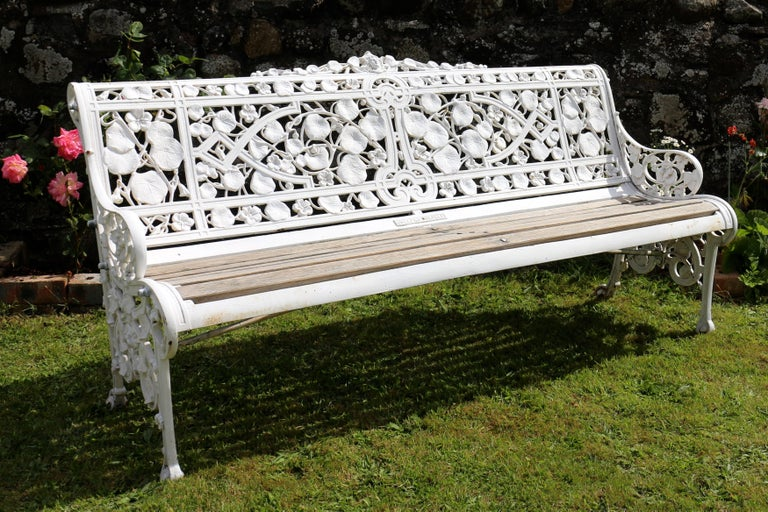 A beautiful Coalbrookdale Nasturtium pattern cast iron garden seat or bench dating to circa 1870. The pierced back and sides with a naturalistic design of intertwined nasturtium leaves, flowers and seeds watched over by a classical mask. With bronze