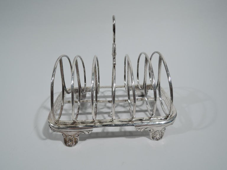 Victorian Georgian sterling silver toast rack. Made by Charles Thomas Fox in London in 1838. Seven double hoop partitions; central partition has ring handle with scroll and shell mount. Rectangular frame with curved corners and central partition; 4