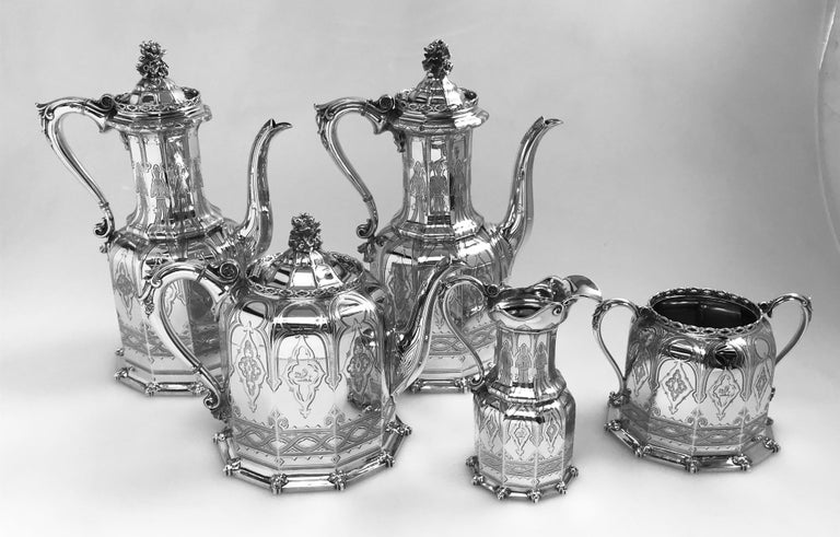A 5-piece silver tea and coffee set hallmarked in the year 1853 in Birmingham, England by the internationally renowned firm of Elkington & Co. The set is in the neo-Gothic style that was popular in the mid-1850s, and consists of two coffee pots, one
