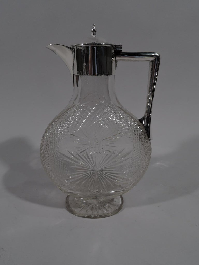 Victorian glass and sterling silver decanter. Made by Grinsell & Sons in London in 1899. Clear glass moon body with flat oval foot. Cut ornament: A star surrounded by diaper on front and back, and star on foot underside. Sterling silver collar with