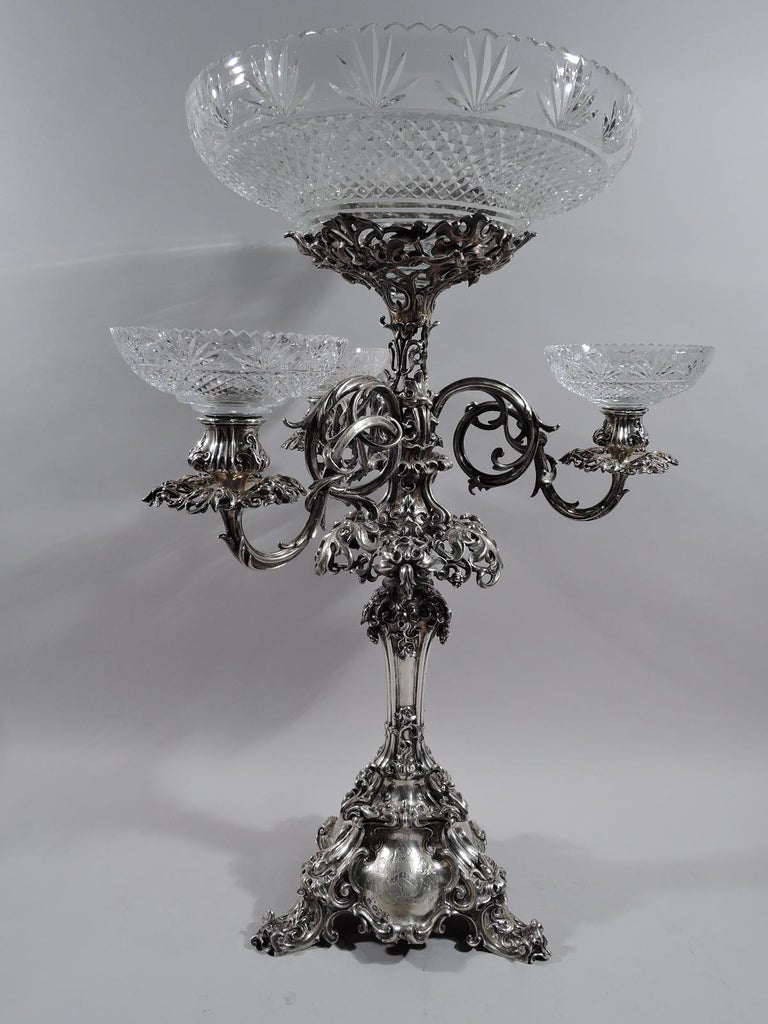 Victorian sterling silver epergne candelabrum. Made by Barnard & Sons in London in 1849.  Shaped shaft with flange and stepped triangular base terminating in 3 scrolled supports. Raised and large central glass basket in support surrounded on 3