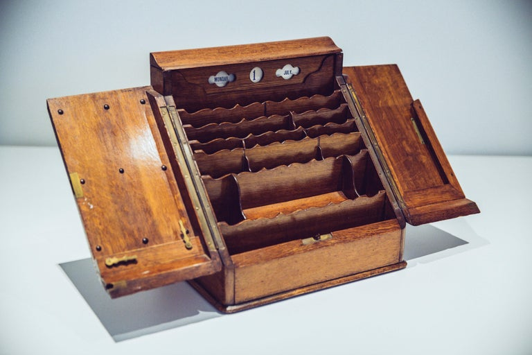 Made in England in the 20th century, this antique walnut desk organizer has its original key and working lock. It is has many compartments and secret hiding places. The top panel holds calendar cards with the days (Monday till Saturday), dates (1st