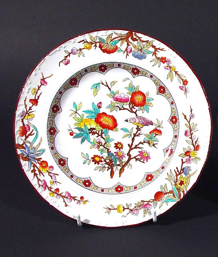 Wedgwood pottery pearlware set of six plates, circa 1870.  The Wedgwood plates are brightly printed with a central scene of two flowering branches with a bird sitting on one. The rim has three similarly bright flowering branches.