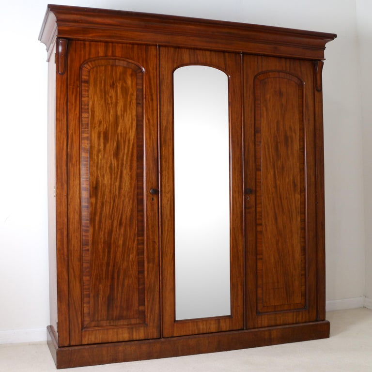 A good quality English William IV mahogany three door wardrobe dating, circa1830. With a moulded cornice above three arched crossbanded panelled doors which open to reveal a fitted interior with a full length hanging space, sliding trays and