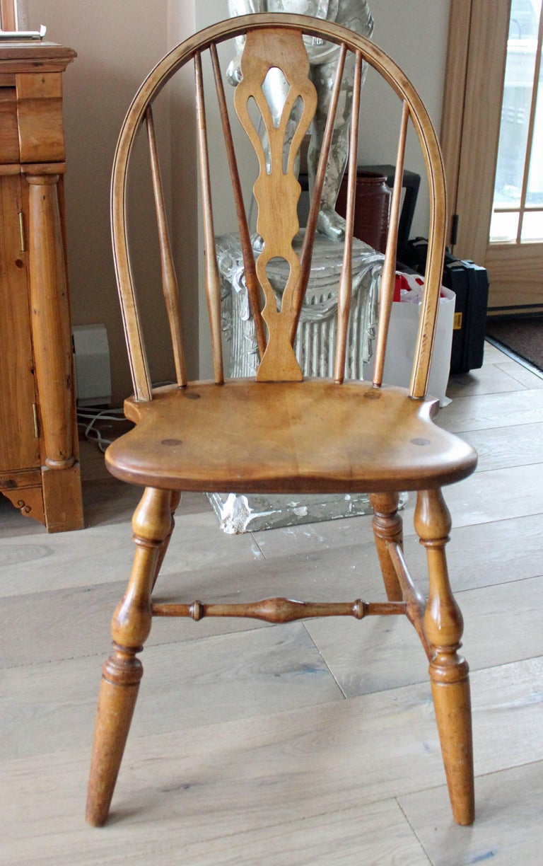 Eight fine English Windsor bow-brace back dining chairs with decorative splat and finely turned legs and stretcher, in ash with coordinated host and hostess chairs with rushed seating details.