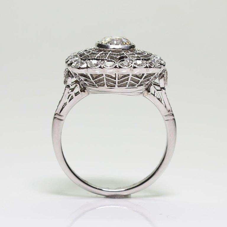 Antique estate platinum diamond Edwardian style engagement ring. Showcasing one Old Mine cut diamond in the center weighing approximately 0.95 carats, having J color grade and VS1 clarity grade. Accented with 30 Old European cut diamonds with