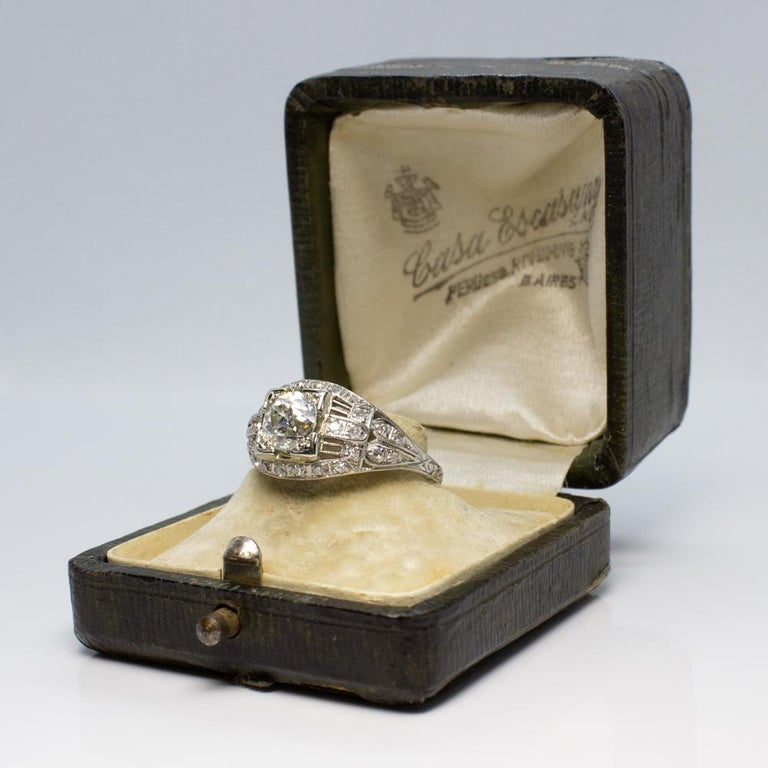 Antique Edwardian diamond platinum engagement ring. Showcasing one Old European cut diamond weighing 1.08 carats, having H color grade and I1 clarity grade. Interspersed with 32 single cut diamonds weighing a total of 0.60 carats having H – I color