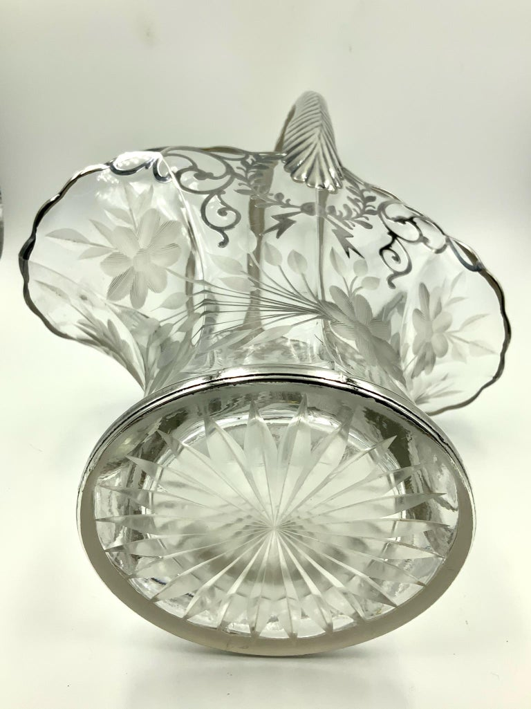 Incredible early 20th century floral wedding basket featuring an etched floral design on the bottom area and a garland scroll sterling silver overlay design on the top part. It is completed by a highly stylized sterling overlay handle. A truly