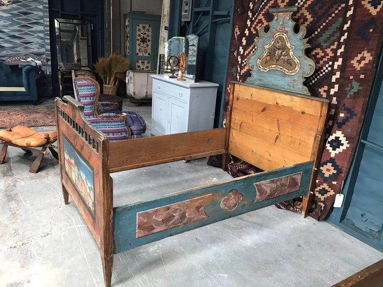 Late 19th century children's bed frame in oak. Features a hand-painted scene of a town square, tapered legs and handcrafted wood decorative detailing.