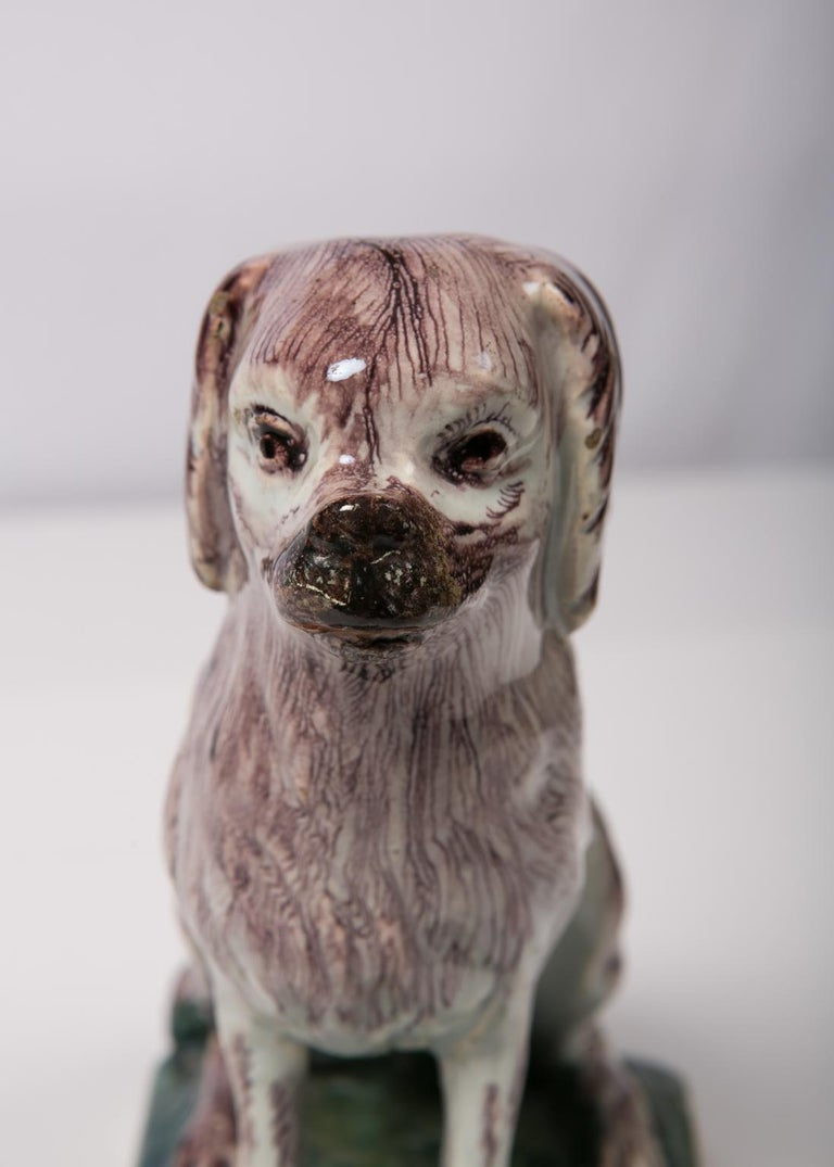 An 18th century Brussels faience figure of a Picardy Spaniel modeled sitting on her haunches looking straight ahead. She has an endearing sweet face, deep set eyes and dark pronounced eyelashes. She has the droopy ears of a spaniel and a bushy tail.