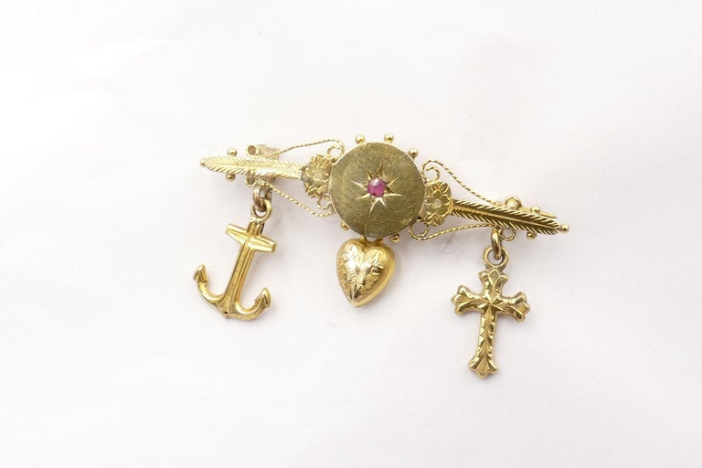 9ct Yellow Gold Victorian Brooch with the 3 hanging charms - an Anchor, a Heart & a Cross,  depicting Faith Hope & Charity. It features one reddish-purple Ruby in the centre of the Bar, eye clean & of medium tone. The Brooch has Foliate detailand