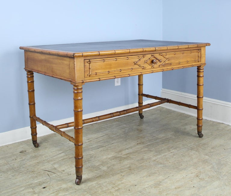 A wide and comfortable French faux bamboo desk with new dark brown leather top. Nice roomy drawer and attractive bamboo detail on the front. Castors are original and functional. 24 inch apron height is good for knees.
