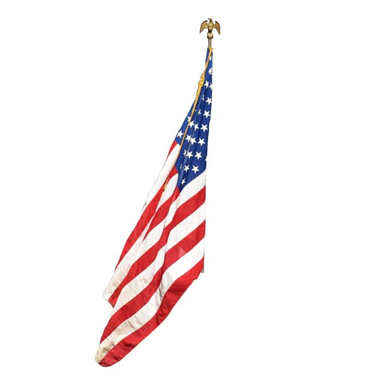 Monumental 50 star American Flag with antique Federal Eagle brass and wood pole. A patriotic piece suitable for any home. This set includes both a vintage American Flag as well as a antique Federal eagle brass and wood pole. The pole is from the