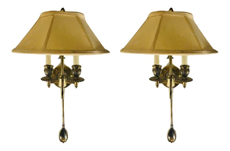 A 1970s timeless pair of Federal style cast brass wall sconces with two candelabras arms each. The sconces feature fine brass design and comes with the shades.