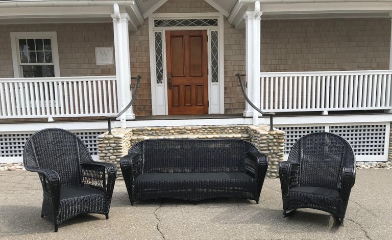 Antique Ficks Reed wicker set in fresh black paint. Sofa, chair and rocker in closely woven pattern with open lattice work under the arms. Pieces are fully skirted for tailored look on all sides. Sofa measures 71