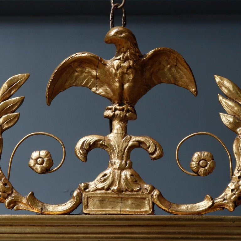 An antique figural Federal style wall mirror offers giltwood frame having crest with spread wing eagle or phoenix flanked by foliate elements and having rosette corners, circa 1920.  Measures: 40
