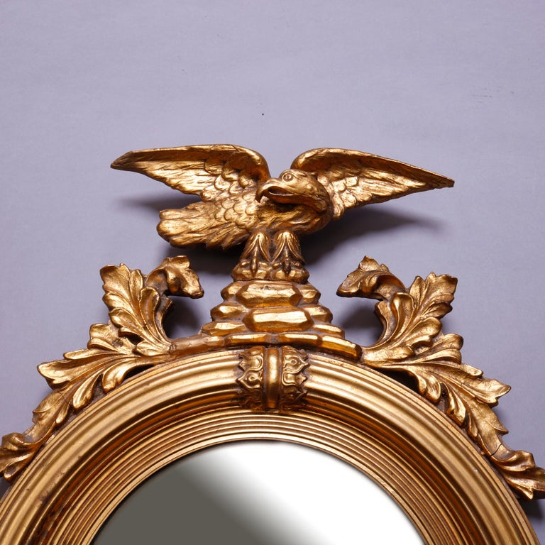 An antique figural Federal style figural giltwood wall mirror features crest with eagle flanked by acanthus surmounting round convex bullseye mirror with reeded frame having foliate decoration, 20th century  ***DELIVERY NOTICE – Due to COVID-19 we