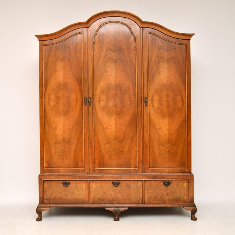 Antique figured walnut three door wardrobe dating from the 1890-1900 period & in very good original condition. It's Queen Anne style & is good quality with fine dovetails in the drawers. This wardrobe has a double arched shaped top, three figured