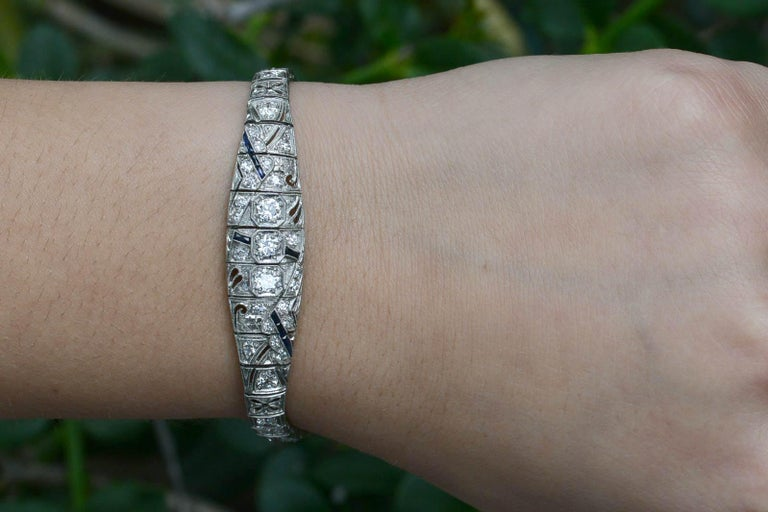 A sleek, geometric Art Deco platinum bracelet adorned with filigree and over 3 carats of fiery old European cut diamonds. These antique cuts with larger, chunky facets are so juicy and the links drape so softly on the wrist. The asymmetrical design