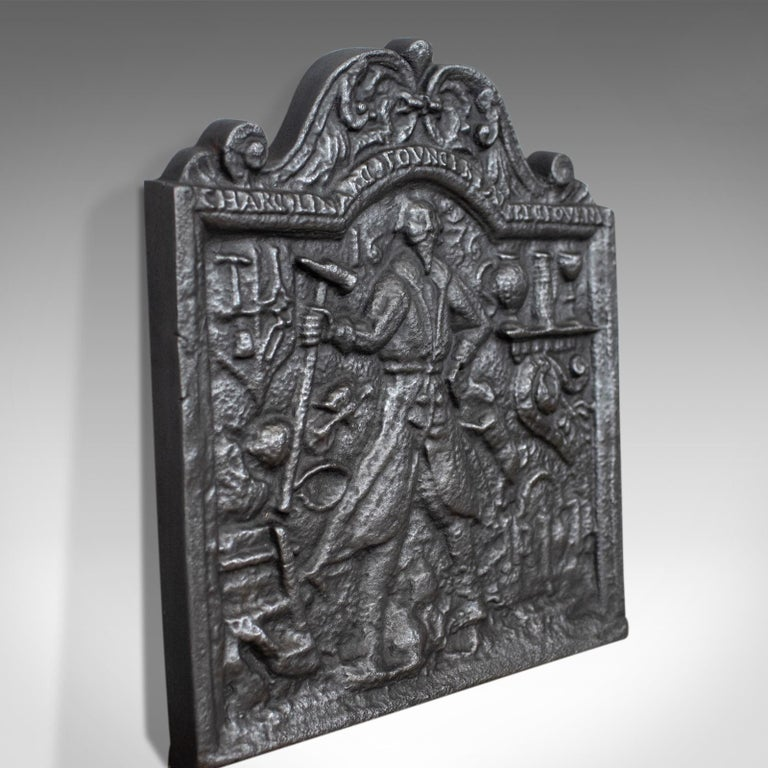 This is an antique fire back, an English, Victorian, cast iron fire plate from the late 19th century dating to circa 1900.  Heavy fire back in cast iron with a graphite finish Scrolled, shaped top over oblong plate Casting of a mason in his