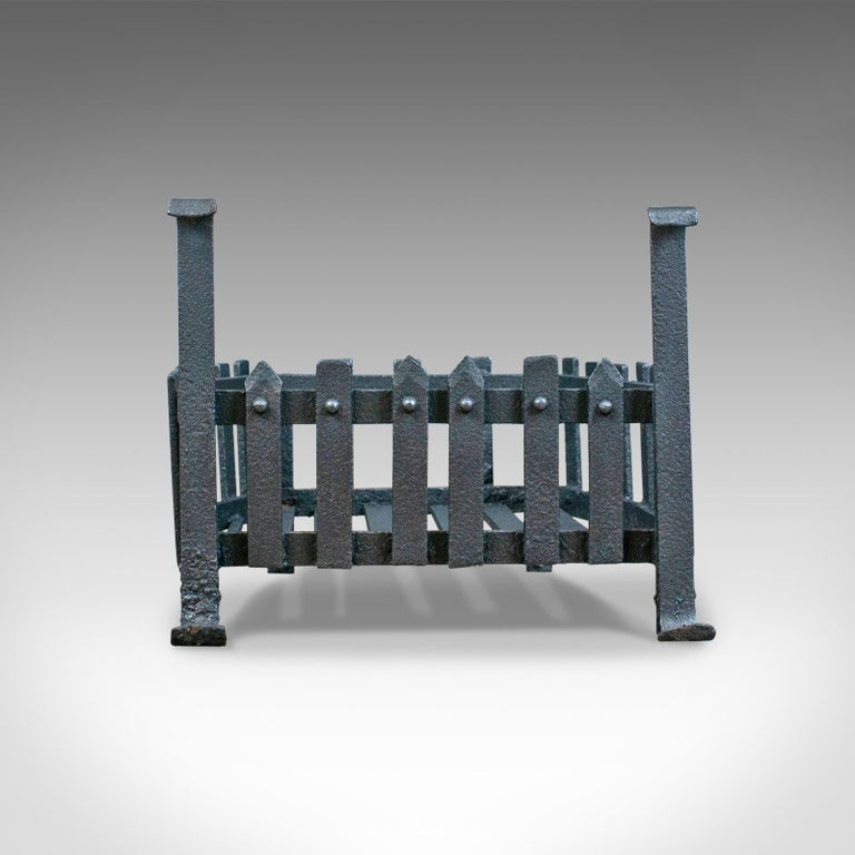 This is an antique fire basket, a free-standing Victorian fireplace grate in iron dating to the late 19th century, circa 1900.  Mid-sized, shaped at the rear to fit snugly into aperture Suitable for all fuel types In hand forged iron with dark