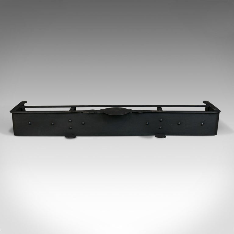 """This is an antique fire surround. An English, Victorian fender hand crafted in iron dating to the late 19th century, circa 1900.  Large fire surround (136cm 53.5"""" wide), to compliment a grand fireplace Attractive button rivet construction with"""