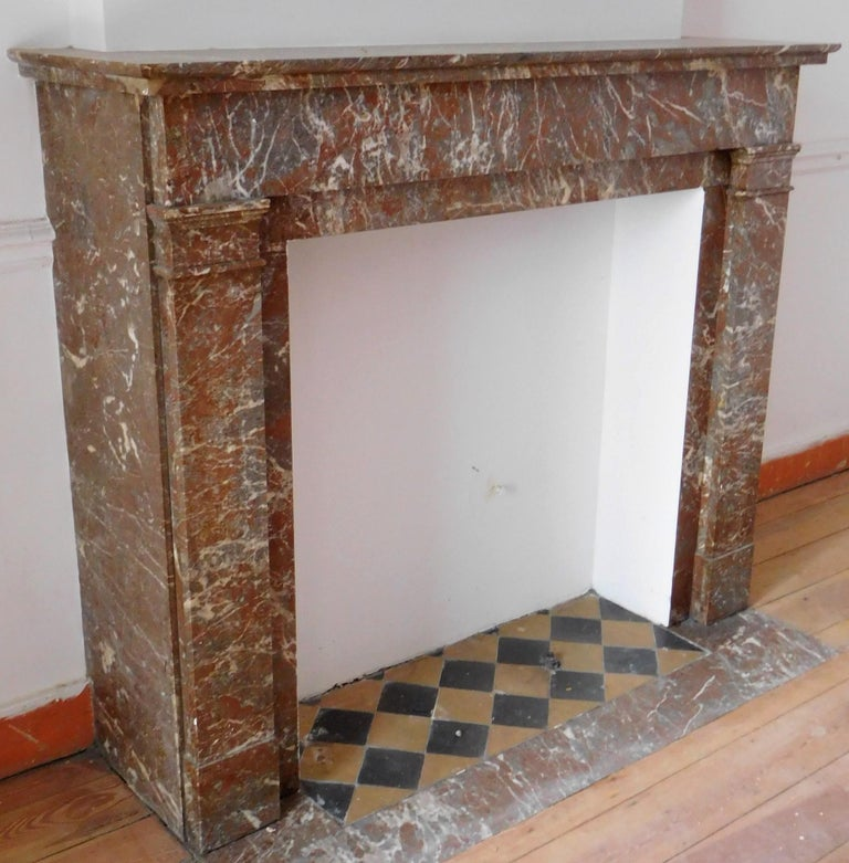 This beautiful antique fireplace in a Belgian Red marble was made in the Art Déco style. The sleek lines of this fireplace provides a subdued, quiet ambiance. The powerful color of the marble is sufficient to be impressive.  The 'Art Deco Bronze'