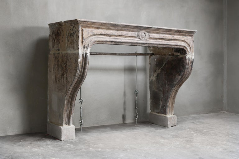 This elegant antique fireplace is made of French limestone and dates from the 19th century! The fireplace is in the style of Louis XIV, this is characterized by beautiful lines and often with an ornament in the middle. All our fireplaces are unique