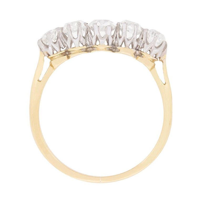 This two-tone Edwardian era five stone diamond ring showcases a lovely quintet of old cut diamonds set horizontally and graduated from centre.  The diamonds are claw set in their original platinum mountings, which were handmade around the turn of