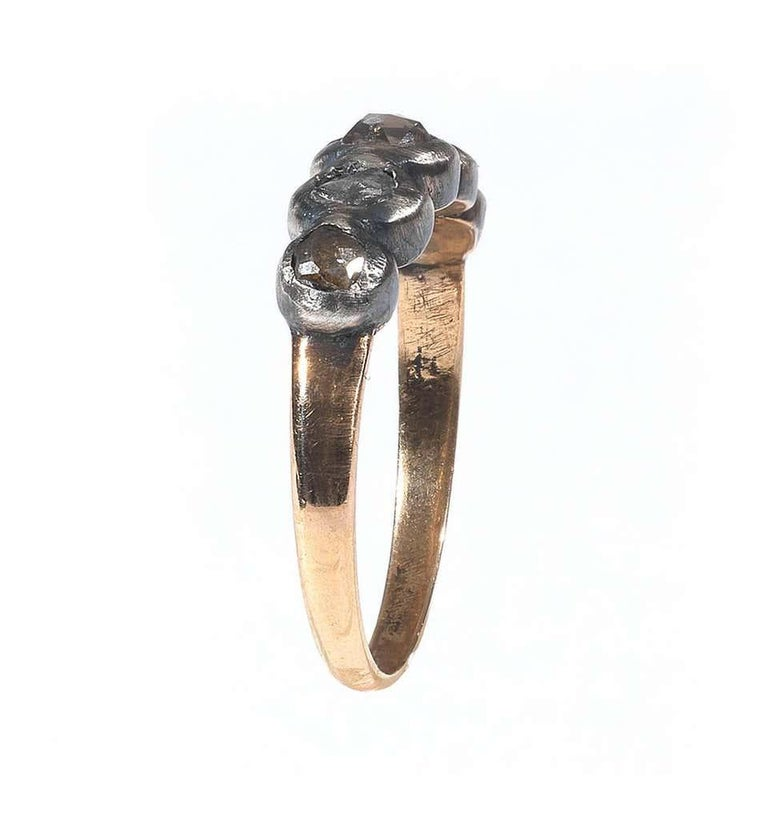 The silver topped collet set five stone rose cut diamonds to a plain yellow gold band.  Finger size: 8.5  Weight: 2.9 gr