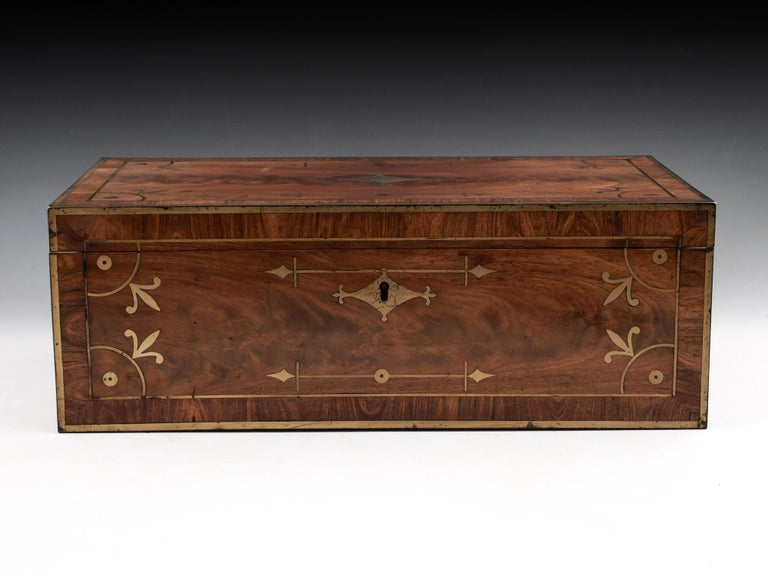 Writing box by David Edwards.  Brass-bound and veneered in flame mahogany with kingwood crossbanding. The interior has three lids and two inkwells. Has its original, almost intact leather with unusual gold tooling which mirrors the exterior brass