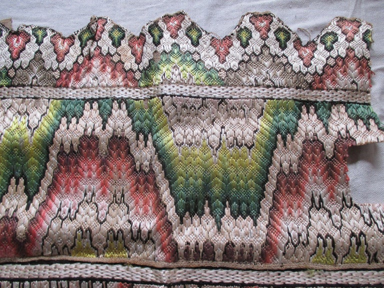 Antique flame stitch textile fragment Pattern: Reflections. With four horizontal bands. Top and bottom ends in a zigzag design. Center two band repeat the designs in shades of gold, yellow, green, orange and tan-taupe. Size: 18.5