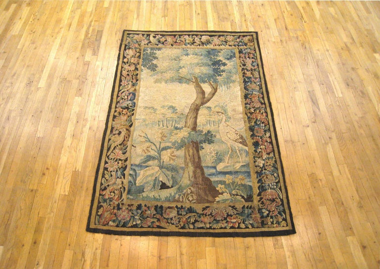 An antique Flemish verdure landscape tapestry panel from the 18th century, envisioning an idyllic setting with a stately tree and an exotic bird in the midst of verdant foliage. A tranquil scene in the tradition of the verdure tapestry, coming from