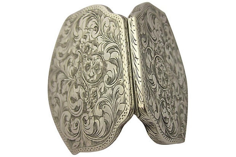 Italian 800 silver floral designed engraved compact with scalloped sides.   On both sides the compact has a basket full of flowers engraved in the middle radiating from the basket is scrolling leaves / vines. The compact has the original powder