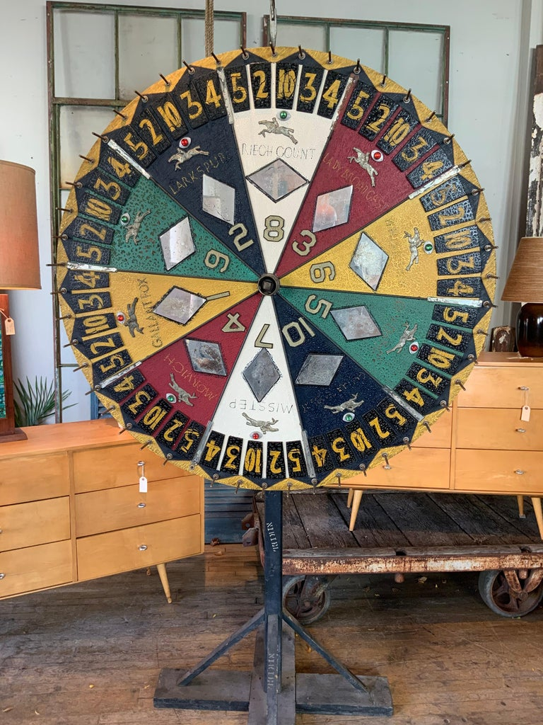 A stunning antique Folk Art horse race betting spinning wheel, circa 1930s handmade with beautiful graphics and design and color. Retains its original clacker attached with a large leather tab. Spins perfectly.