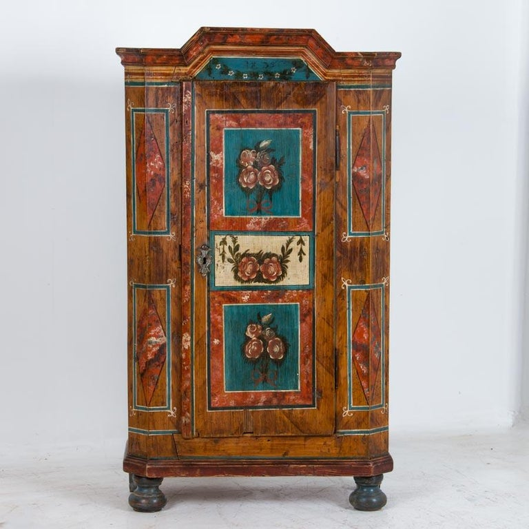This is an outstanding painted armoire due to the high quality and detail of the original paint. The soft, gentle colors used to paint the delightful floral motifs are exceptional in both detail and quality, and contrast perfectly against the amber