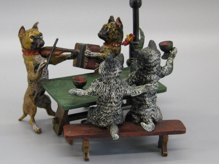 Very tough to find Vienna bronze sculpture by Franz Bergman. The sculpture is of cats and dogs sitting at a table. The dogs are playing musical instruments and the cars are drinking and singing. The bronze figure dates from the late 1800s-early