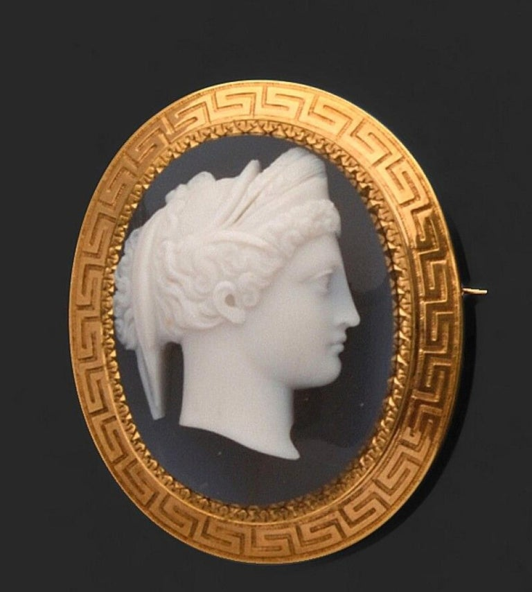 CAMEO on agate decorated with a young woman in profile turned to the right, richly chiseled hair, 750 / °° yellow gold setting decorated with Greek frame. XIXth century. 4.8 x 4 cm. Gross weight: 24.6 g.