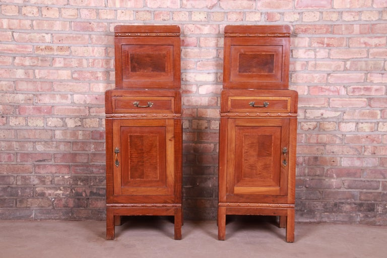 A gorgeous pair of antique French Art Deco nightstands  France, circa 1920s  Mahogany, with satinwood inlay, marble tops, and original brass hardware.  Measures: 15.75