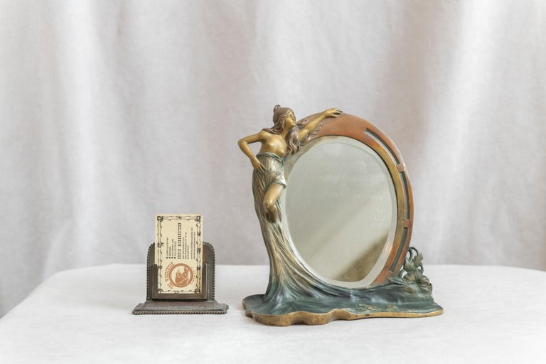 A fine example of a figural art nouveau mirror in bronze. A young woman holding a beveled mirror with a flat area below covered in flowers. We especially loved that flat area for it's attention to the detailing of the flowers, and it's rich factory