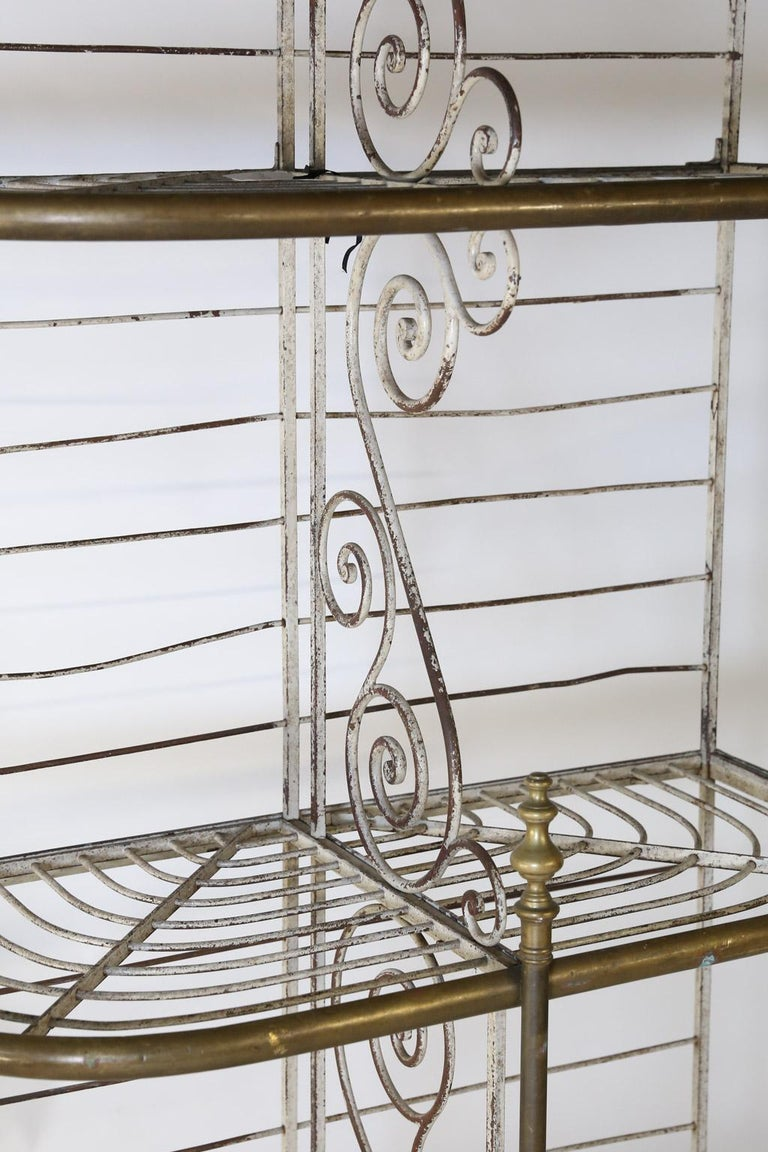 Found in France, this beautiful antique bakers rack is made with iron and brass. Perfect in scale and size for any home, this piece offers three tiers divided by scroll work through the middle of each tier offering six divided spaces. The piece