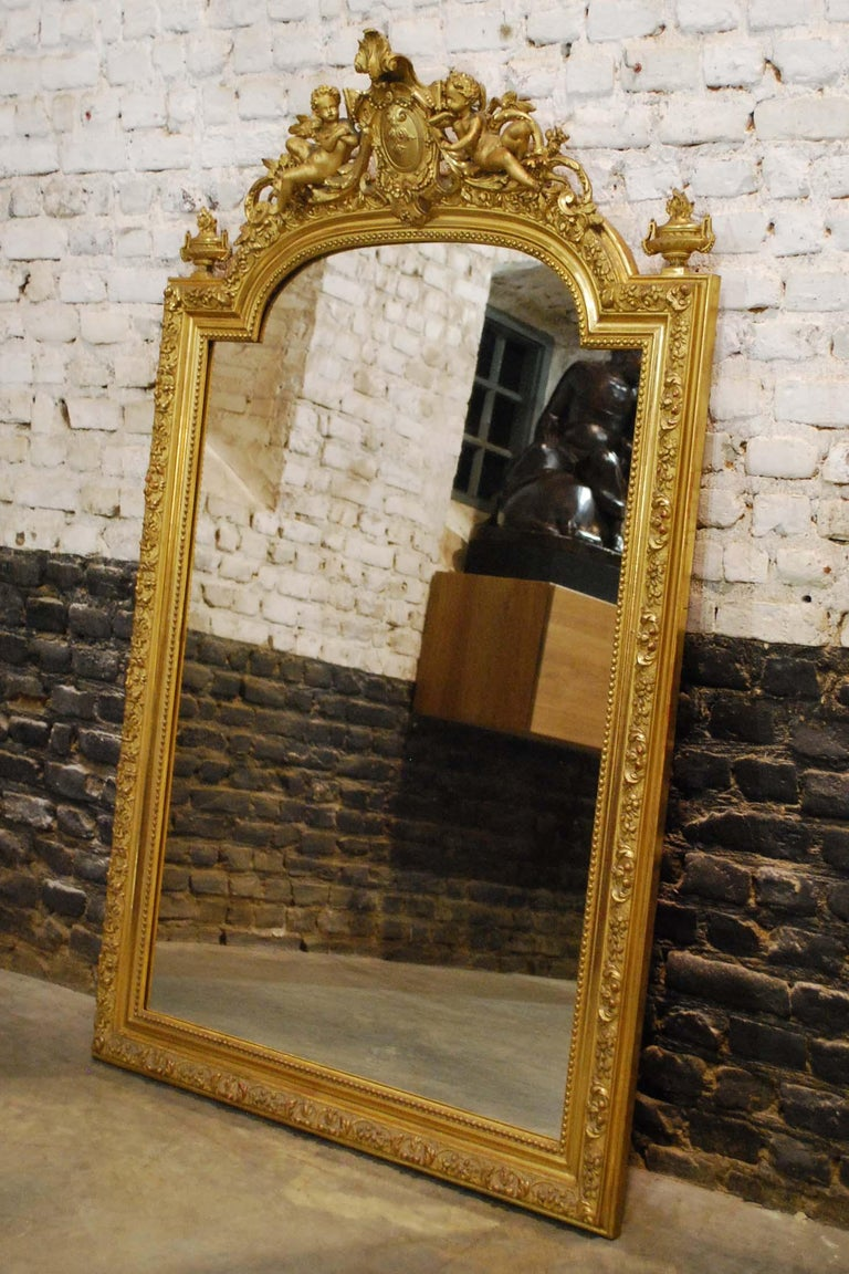 This beautiful Baroque golden mirror is made in France, circa 1850.  The frame has an arched top and is enriched with intricate decorations. The mirror has an ornate crest with a central medallion flanked by two angels or putti and acanthus and