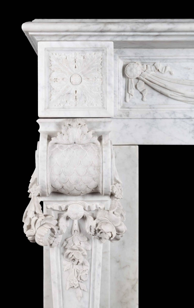 An antique French Carrara marble mantelpiece in the Louis XVI style. The swags of drapes frieze, centered by a plaque that is carved with a classical urn and arabesques. The square foliate paterae corner blocks rest on console jambs, which are