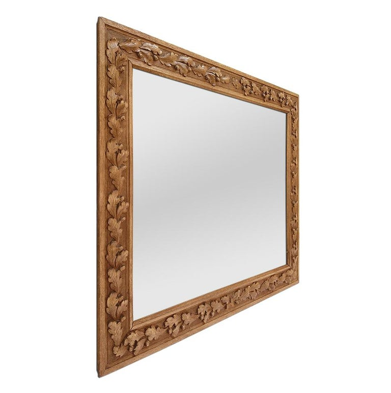 Antique French carved wood mirror with decor oak leaves and tassel nuts. Antique carved oakwood frame, circa 1930 (Antique frame width: 8.5 cm / 3.34 in.). Modern glass mirror.