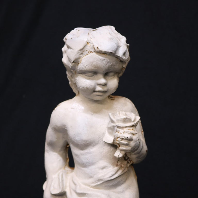 A French figural garden sculpture offers painted cast iron construction and depicts young boy or cherub holding a flower and walking in countryside setting, circa 1940  Measures: 19