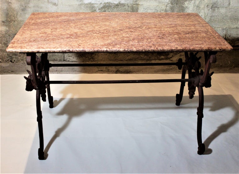 This antique French cast iron butcher's or conservatory marble-topped table was made in the late 19th century in the Victorian style. The base is very ornately cast with scrolled decoration and two figural cow heads on each of the trestle side
