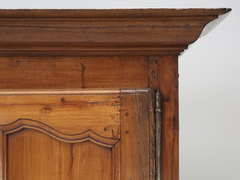Antique French bonnetiere made from solid cherrywood and probably was constructed in the late 1700s. The cherrywood, of our bonnetiere or small armoire or cupboard, has a beautiful and natural patina to it. Both the upper and lower doors of our