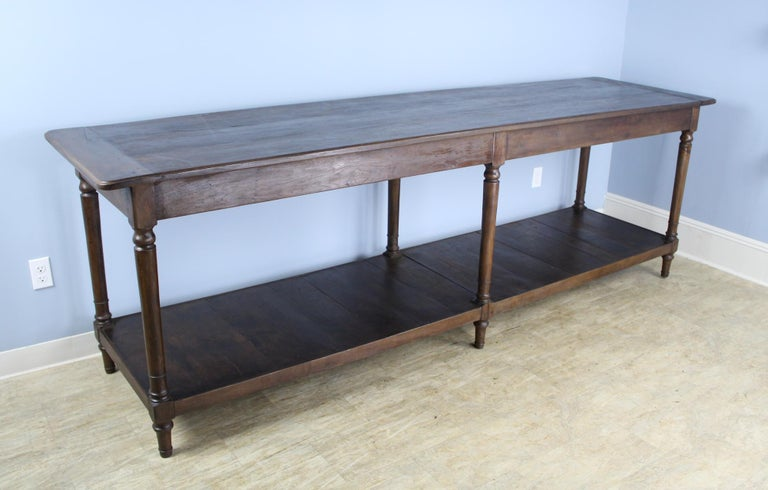 A very long, fabulous French chestnut draper's table, originally for use by a tailor or seamstress. Legs have good turned detail and nice patina. Top has been refinished for a smooth clean look. Would work well as a room divider or as a kitchen