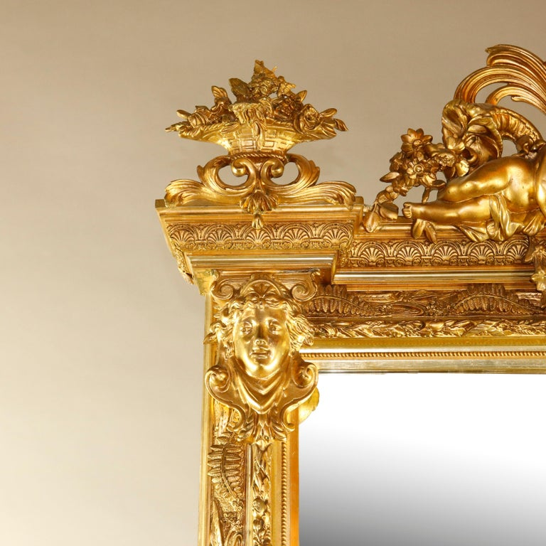 An antique French Baroque style figural pier mirror offers giltwood surround with pierced scroll and foliate crest having central classical female bust flanked by Cherubs and Panier de Fleurs surmounting fern and foliate decorated frame with